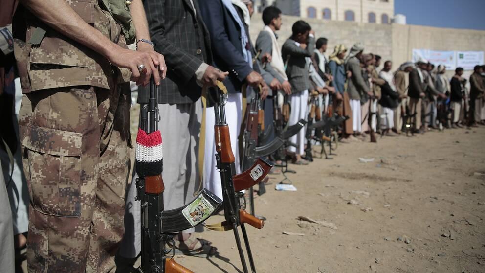 Män står på led och håller i vapen.
