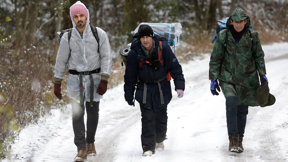 Tre män bär på sin packning i snön på väg mot gränsen till Kroatien.