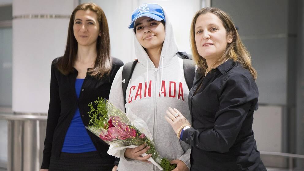 Rahaf al-Qunun, 18, anlände till Toronto flygplats under lördagen och hälsade pressuppbådet tillsammans med Kanadas utrikesminister Chrystia Freeland (höger)