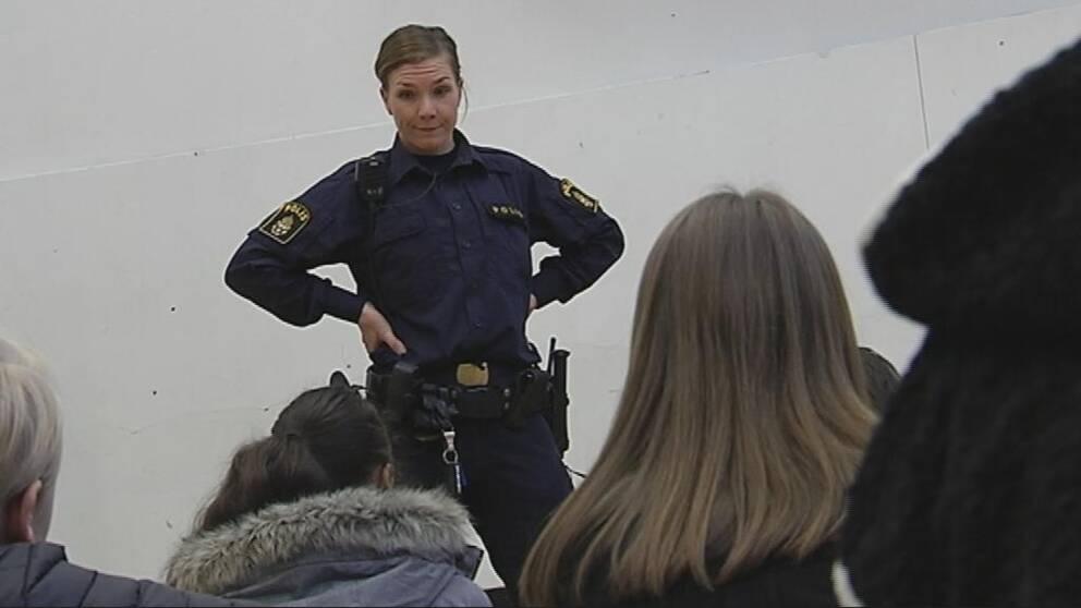 Polis står inför ungdomar och pratar