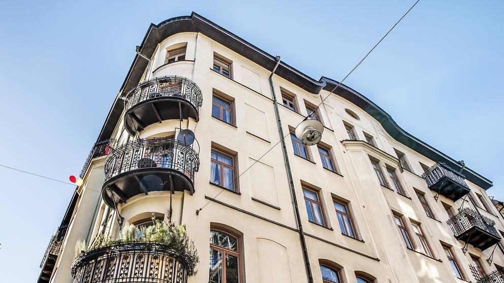 Ett gult bostadshus med svarta balkonger