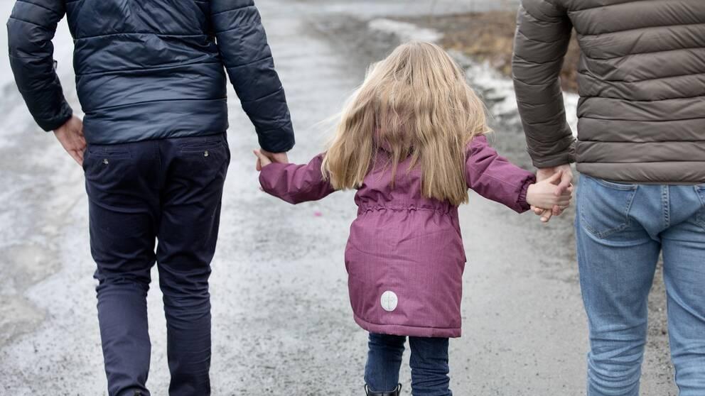 Föräldrar som går med barn i handen.