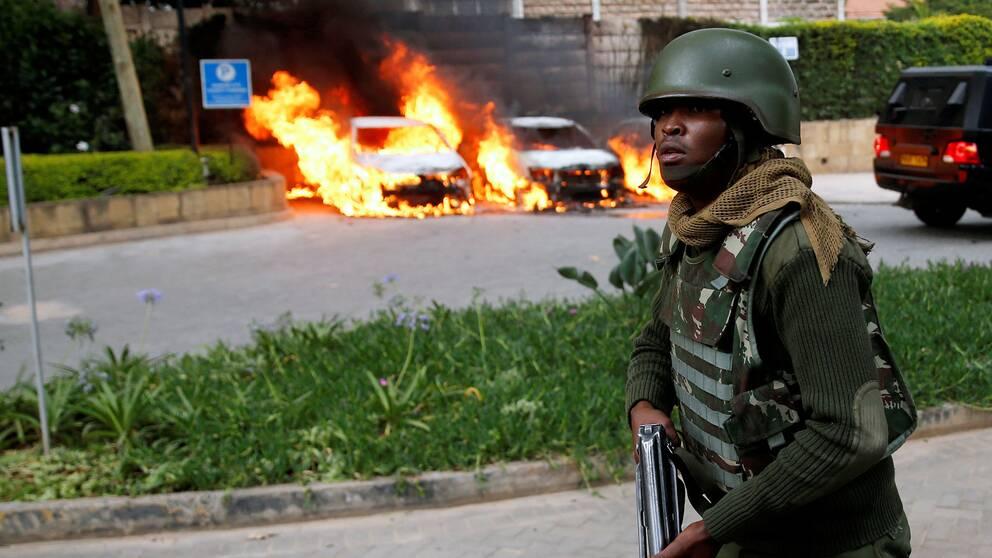 Väpnad polis framför brinnande bilar utanför hotellkomplexet