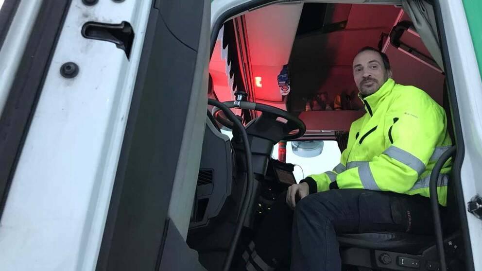 Yrkeschauffören Jan Hallenius sitter i förarsätet på sin lastbil.