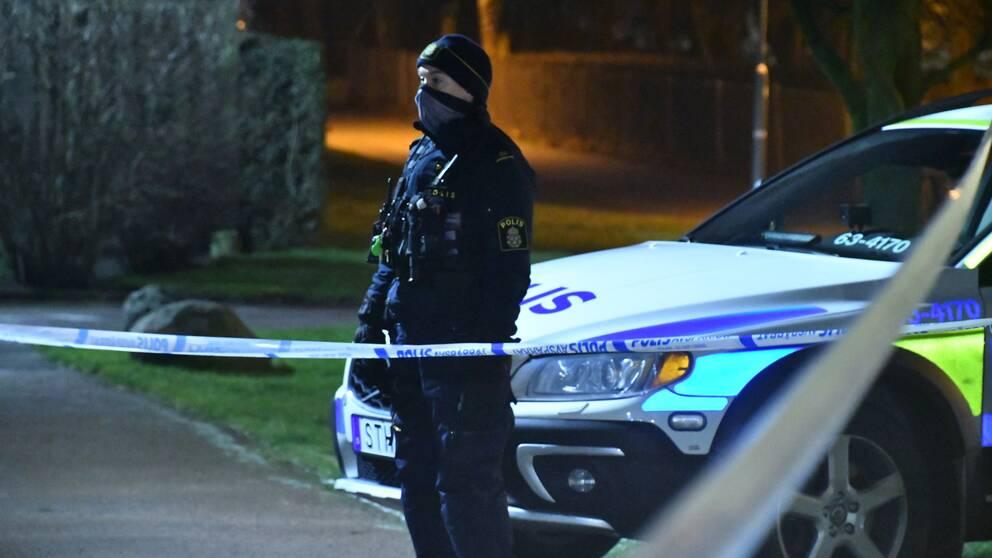 En polis som står vakt i väntan på att teknikerna ska komma till lägenheten under natten till söndagen.