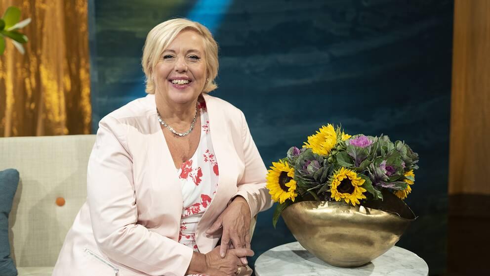 Suzanne Axell, bredvid en bukett med solrosor i Fråga doktorns studio.