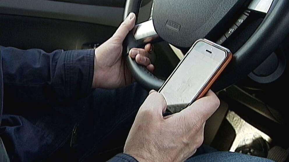 manshänder som håller i ratten i bil och i en mobil
