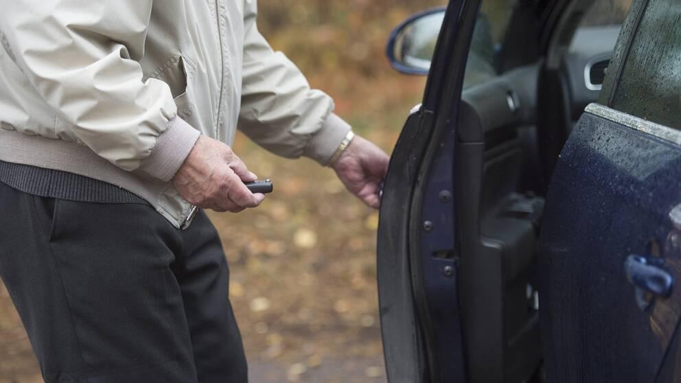 Äldre man öppnar bildörren till en blå bil.