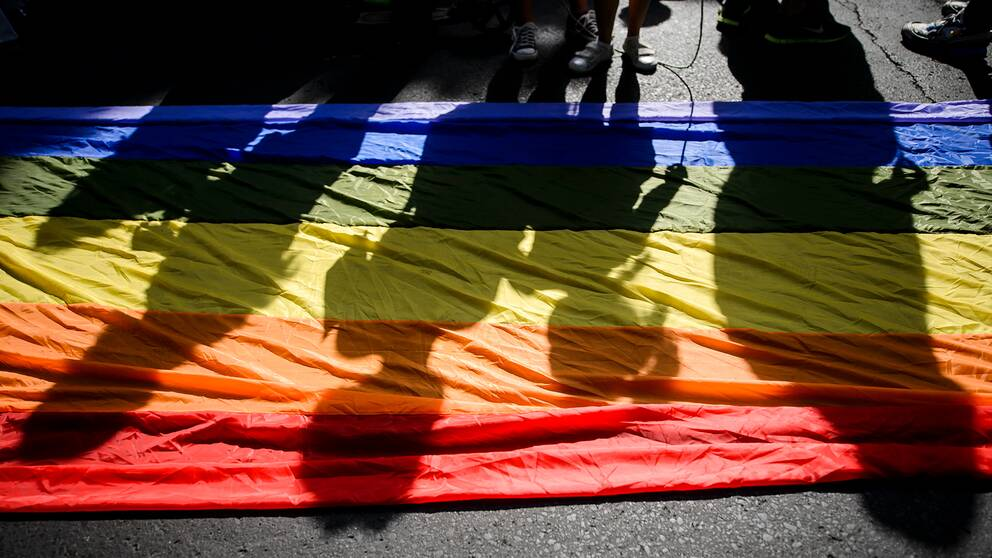 En regnbågsflagga ligger på marken, människors skuggor syns över den.