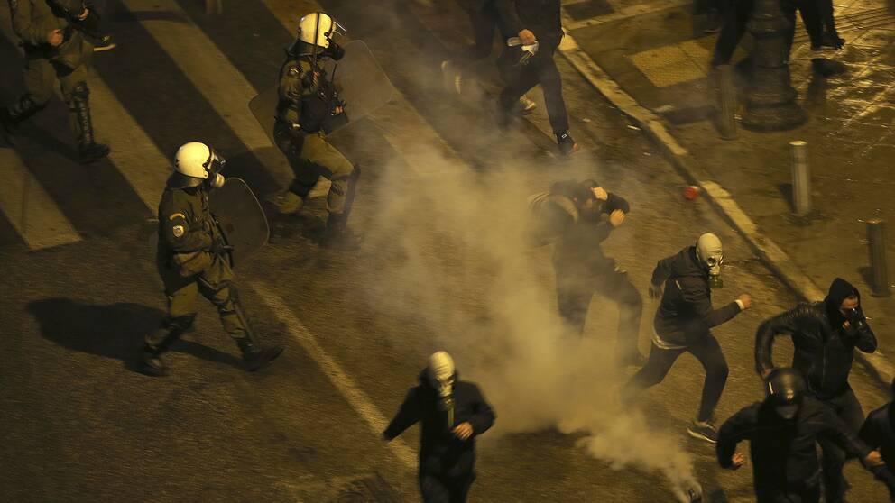 Grekisk polis kastas tårgas mot demonstranter utanför parlamentet i Aten.