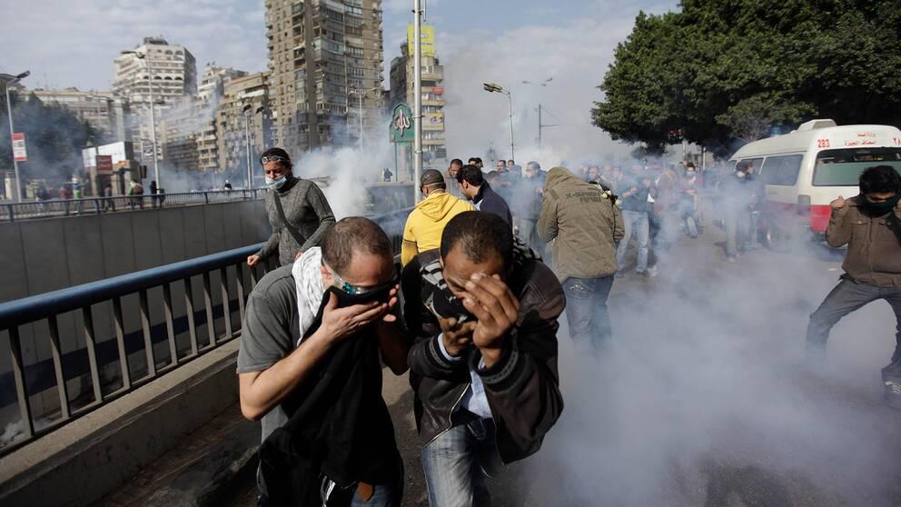 Män flyr undan tårgas i Egypten.