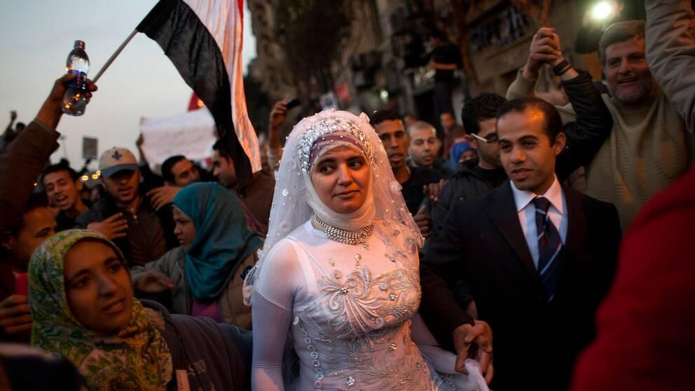 Ett brudpar går genom folkmassan på Tahrirtorget.