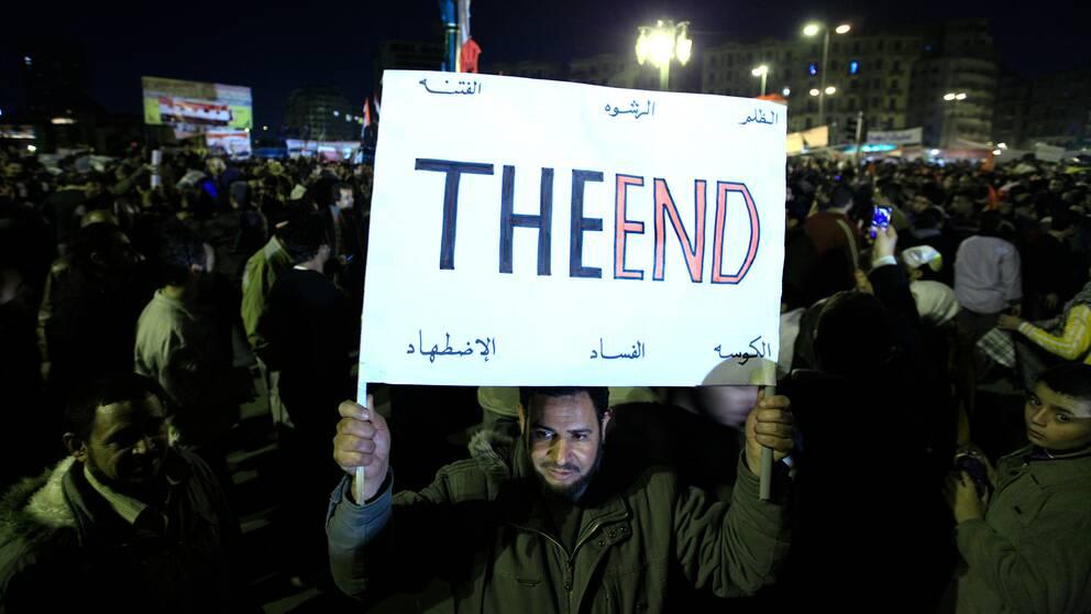 En man håller upp ett plakat där det står: The End