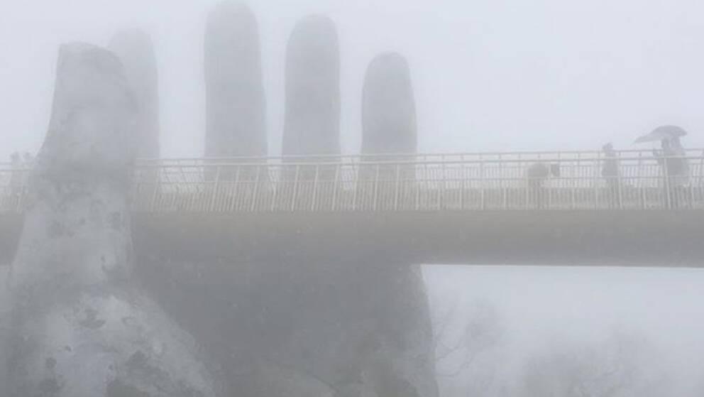 Vid den Gyllene bron i Da Nang i Vietnam kom dimma och regn. De två jättehänder som håller upp bron var knappt synliga, enligt Helen.