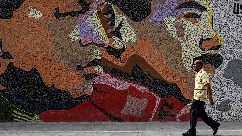 En man går förbi en mosaikvägg föreställande Nicolas Maduro och Hugo Chaves.
