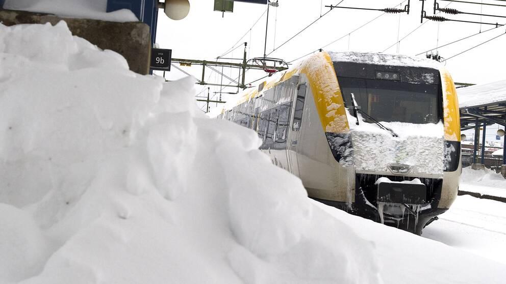 Tåg framför en snöhög på perrongen