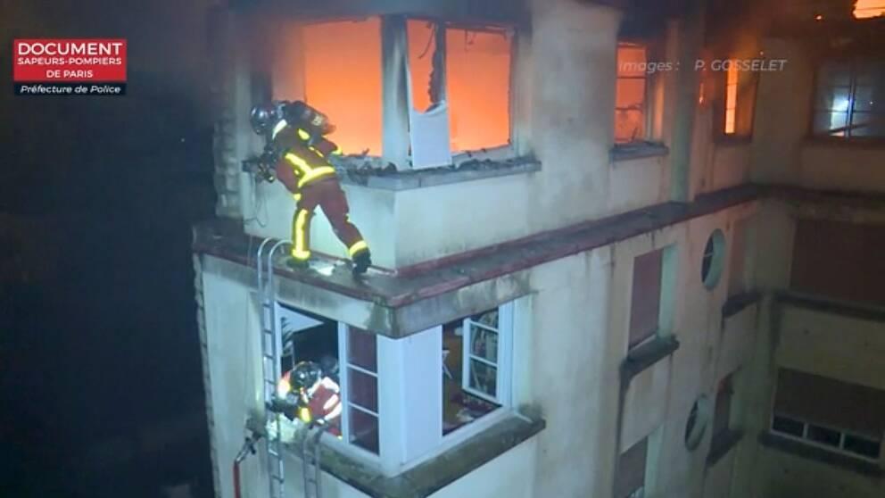 Brandmän klättrar på stegar för att nå de utsatta lägenheterna