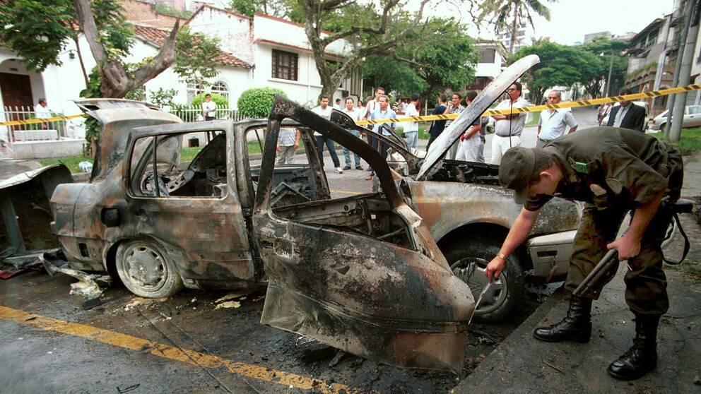 En polis undersöker en bil som sprängts av rånare i Cali i Colombia.