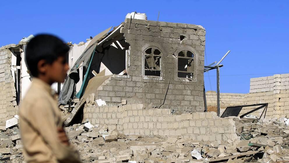 Ett barn bredvid ruinerna av ett bombat hus i Jemens huvudstad Sanaa.