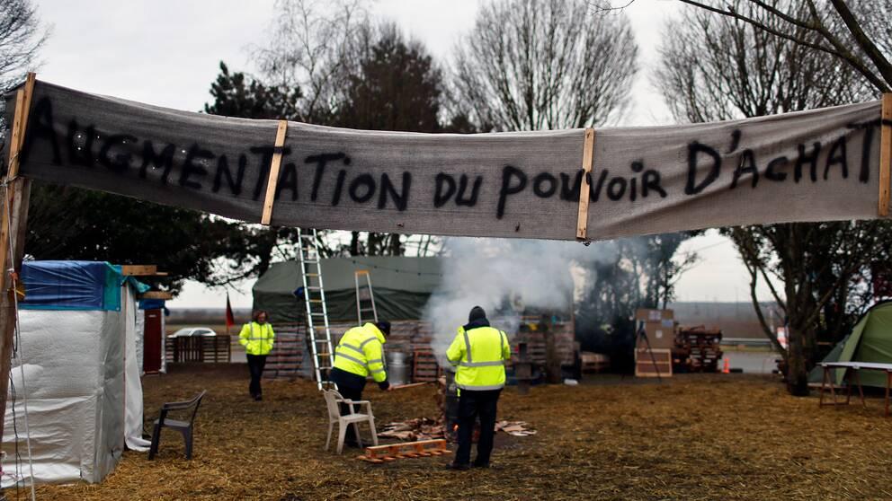 """""""Höjning av köpkraften"""", står det på rondellockupanternas banderoll."""