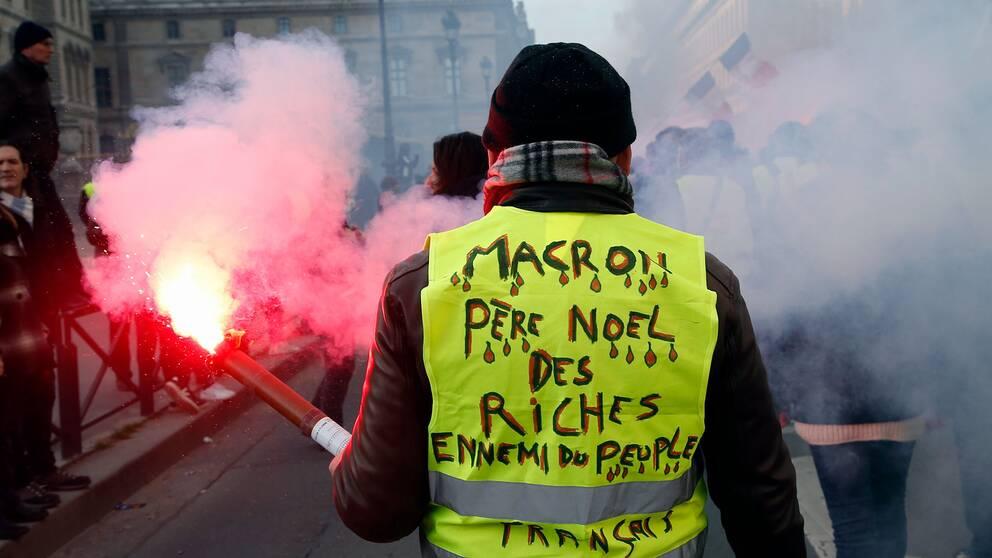 """""""Macron, de rikas jultomte, folkets fiende,"""" står det på demonstrantens rygg."""