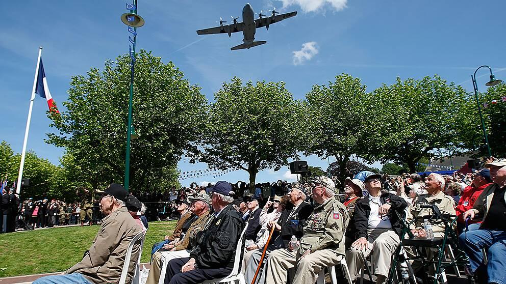Amerikanska krigsveteraner tittar upp mot ett C130 Air Force-plan som flyger över Sainte-Mere-Eglise i Frankrike under en ceremoni för att hedra fallskärmshoppare.