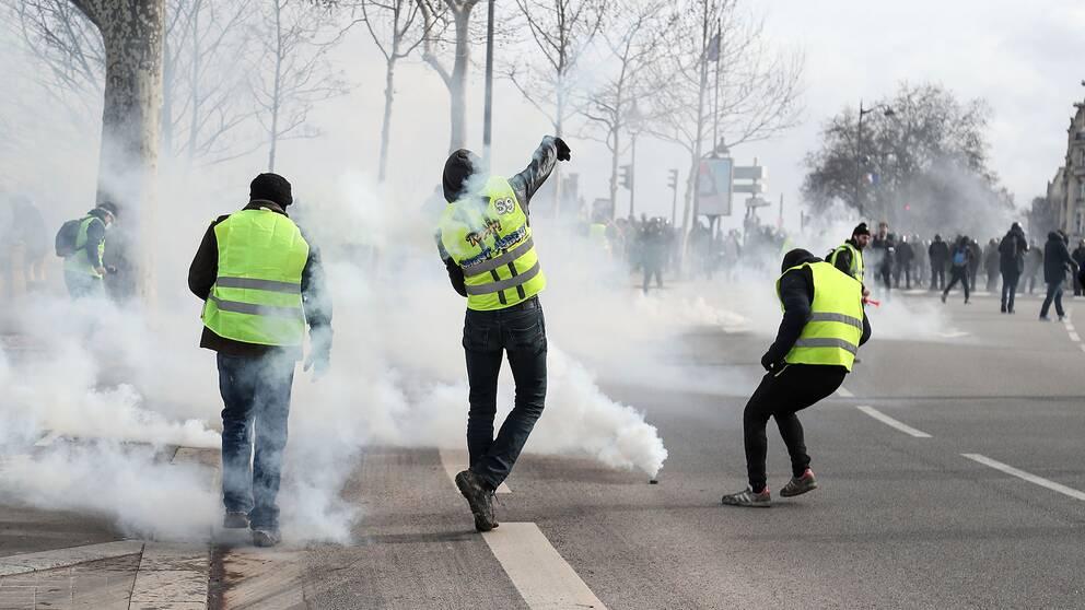 Demonstranter från Gula Västarna i Paris kastar tillbaka tårgasgranater som polisen skjutit