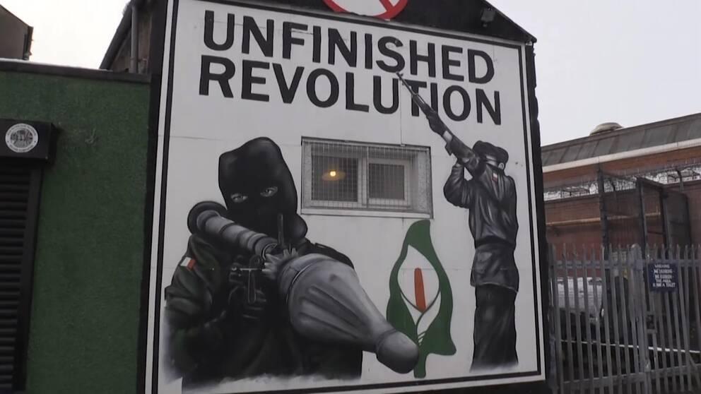 Väggmålning med maskerade men med raketgevär och texten unfinished revolution