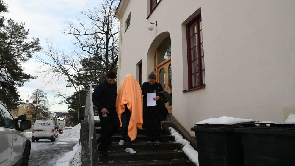 två vakter leder person dold under filt nerför trapp på tingshuset