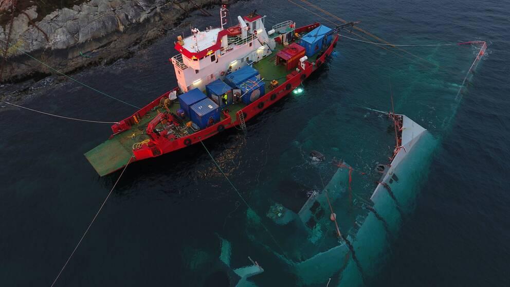 Militärfartyget Helge Ingstad under ytan i Helgefjorden intill ett räddningsfartyg i slutet av november 2018.