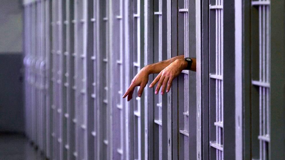 Händer som sticker ut från en fängelsecell.