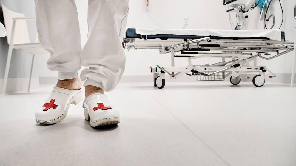 Sjukvårdspersonal med träskor, sjukhussäng i bakgrunden.