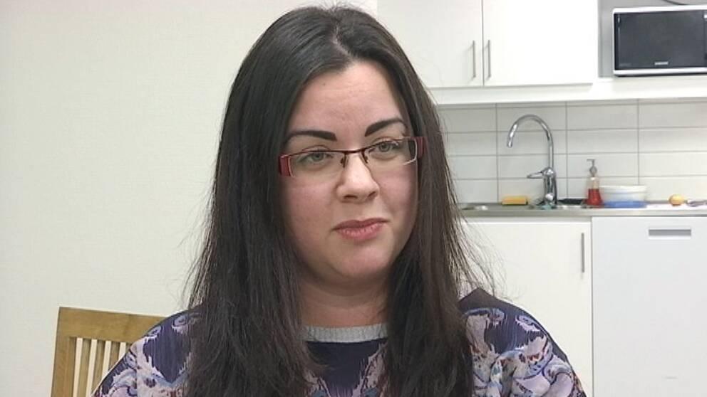 Kvinna med mörkt långt hår och glasögon sitter i ett kök