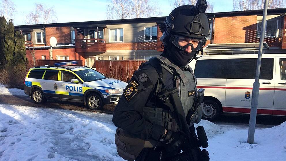 Beväpnad polis framför polisbil och hus i Vivalla.