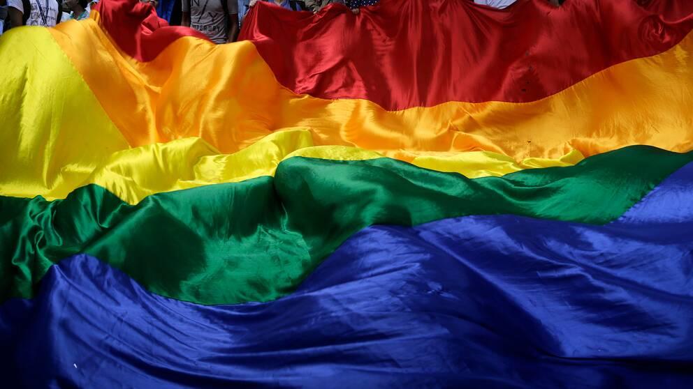 En stor regnbågsflagga hålls upp av flera personer.