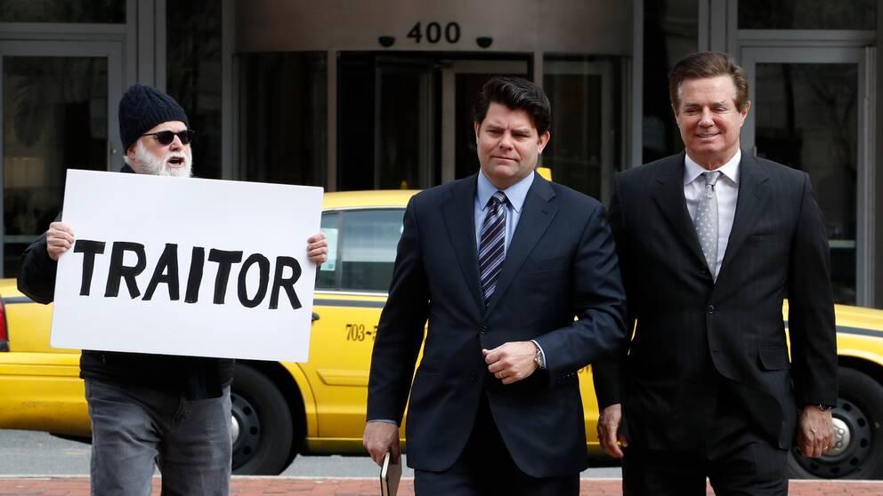 En ensam man protesterar mot Paul Manafort (t.h) medan den tidigare kampanjchefen är på väg till domstolen tillsammans med sin talesperson Jason Maloni.
