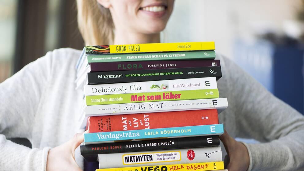 Kvinna som bär kostböcker.