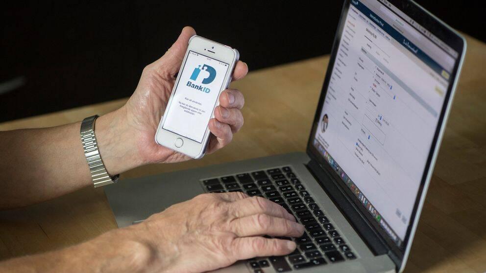 Hand med armbandsur håller i mobiltelefon och har en laptop uppslagen framför sig.