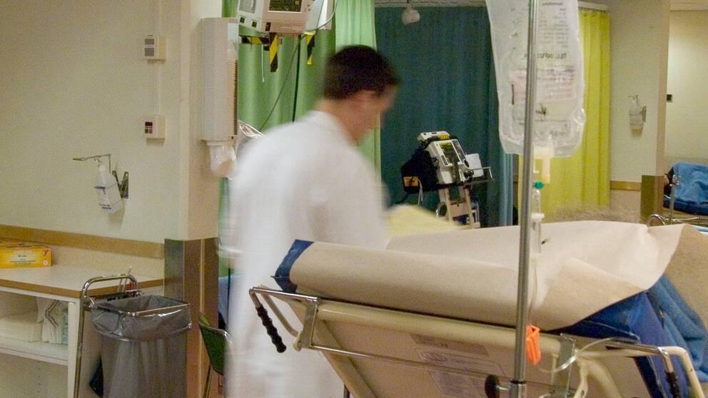 Läkare som skyndar genom sjukhuskorridor.