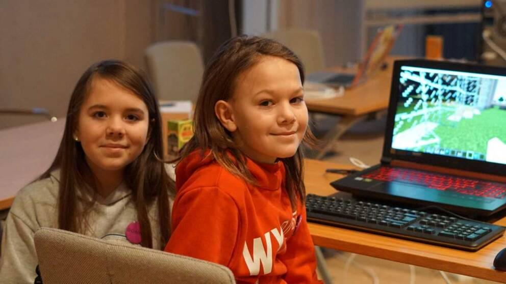 en flicka och en pojke spelar dator