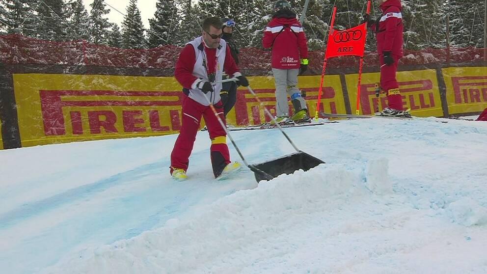man i rödvita kläder skottar snö i skidbacke i Åre under alpina VM 2019