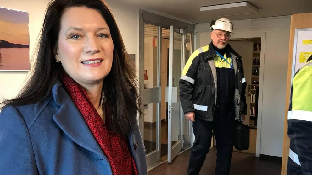 Bild på Ann Linde i förgrunden inne i kubals lokaler i bakgrunden passerar hjälmförsedda och arbetsklädda arbetare.