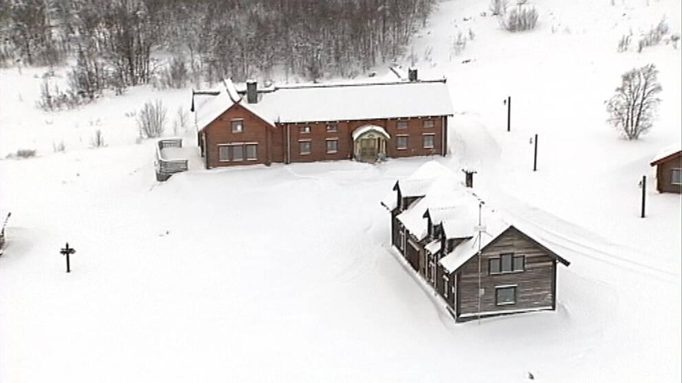 flygbild över Henvålen, två trähus med snö på taken och snö på marken