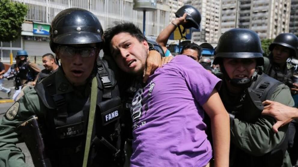 Militärpolis håller venezuelan kring halsen under demonstration.