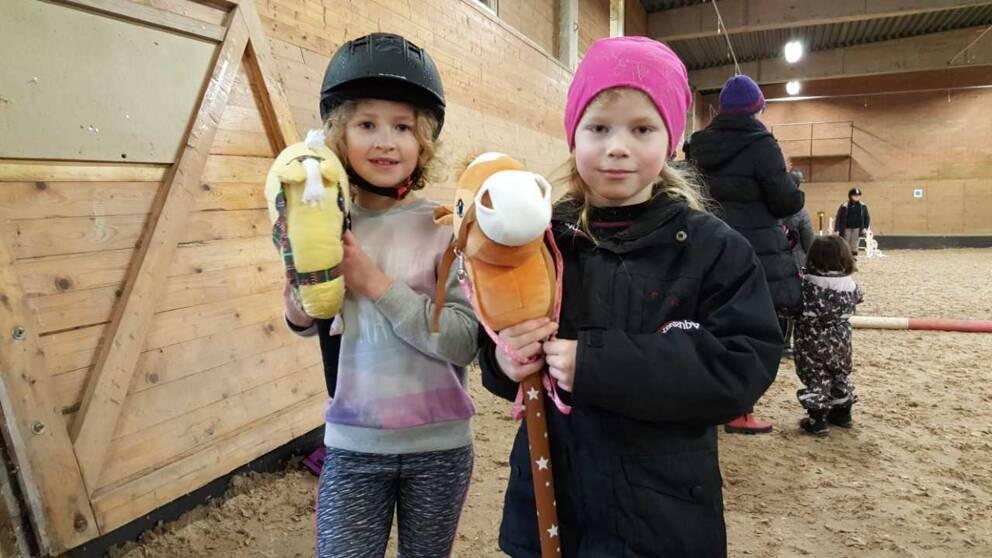 två flickor står med varsin käpphäst
