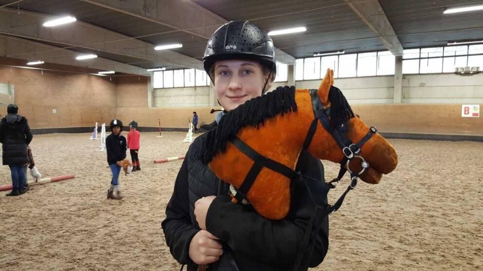 flicka står med käpphäst