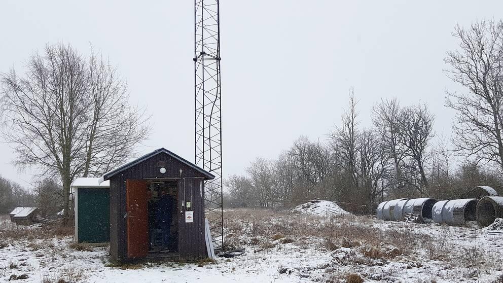 En litet hus ute på landet med en stor antenn bredvid.