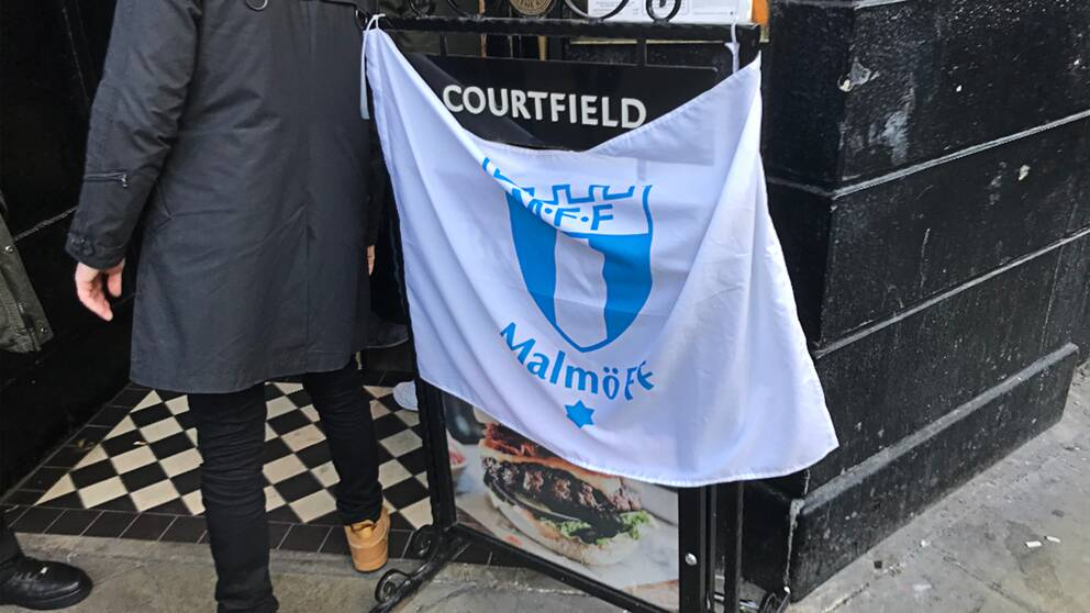 Malmö FF-flagga över en pubskylt.