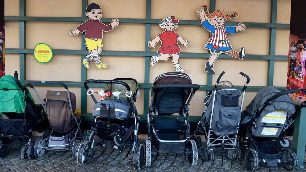Barnvagnar på rad utanför lokal.