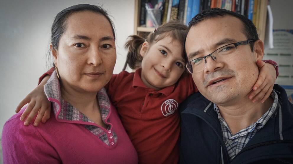 Kvinna och man som har sin dotter emellan sig framför en bokhylla.